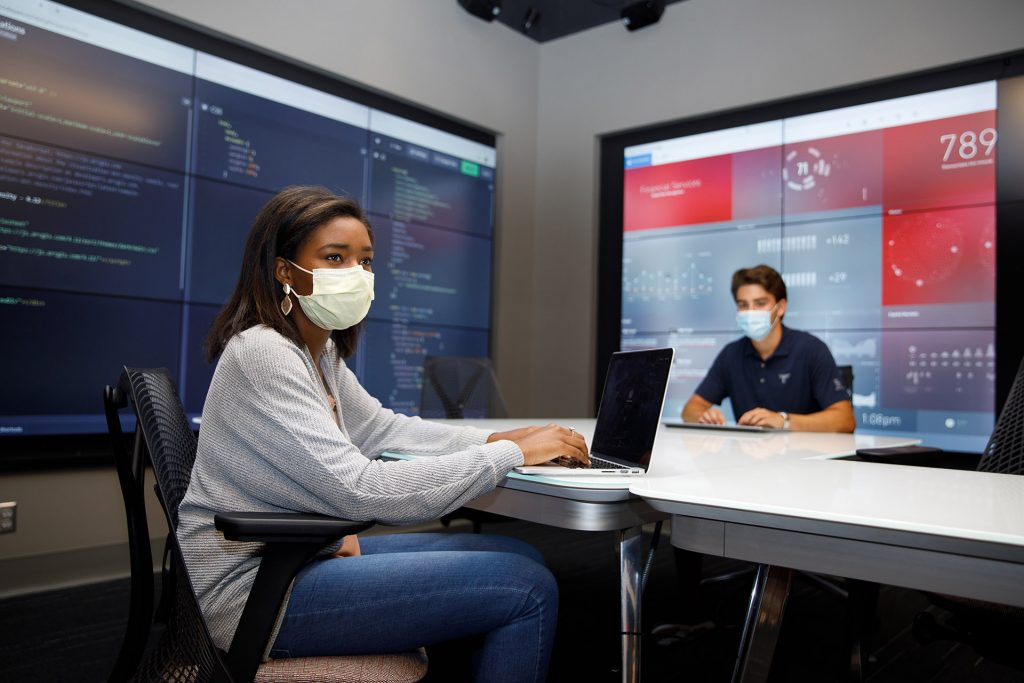 Two students wearing masks work together in the Hewson Analytics Lab