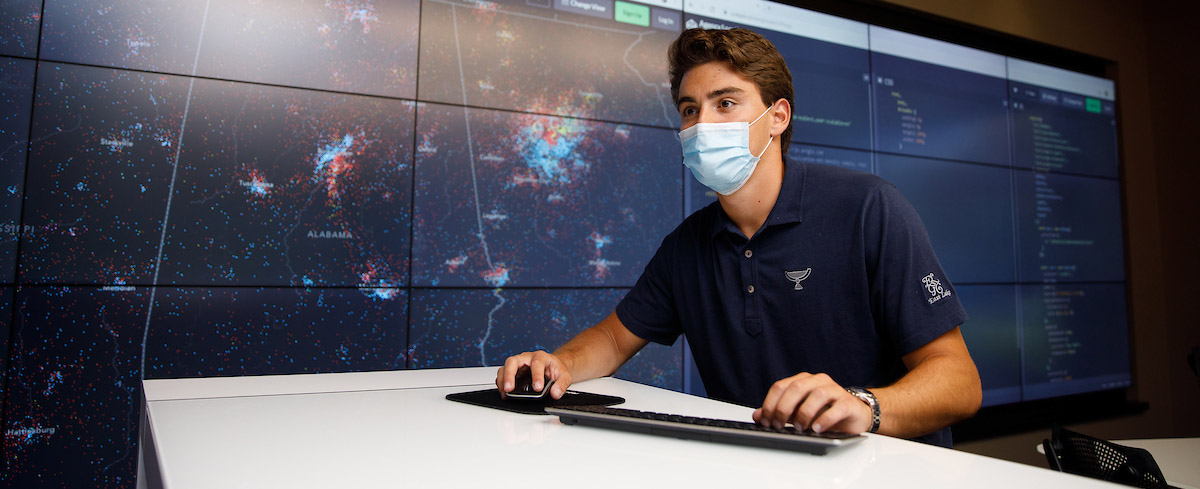 A student wearing a face mask works with a computer in the Hewson Analytics Lab