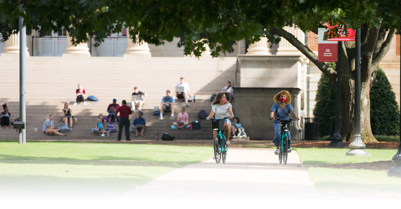 Two students wearing masks bicycle on the quad.